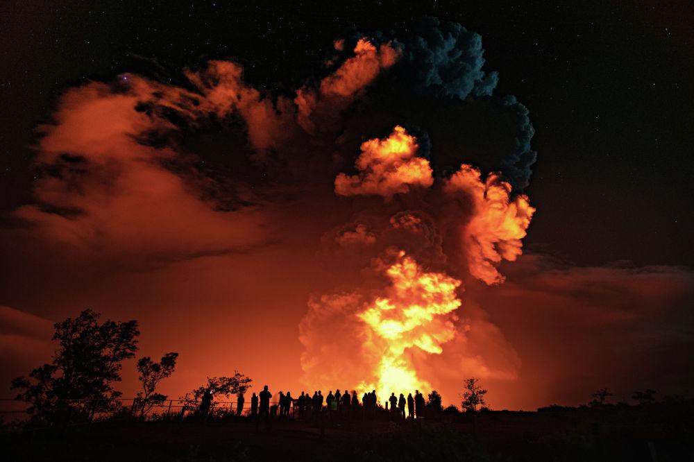 Люди наблюдают извержением вулкана Килауэа на Гавайях на Большом острове. 20 декабря 2020 года