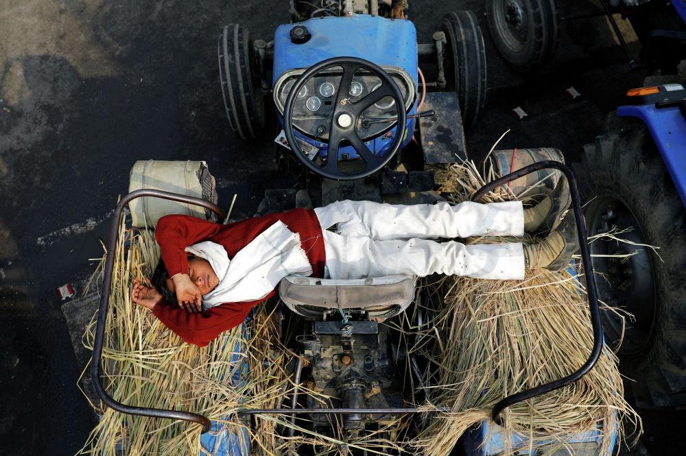 Сын фермера спит на тракторе на месте протеста против новых фермерских законов на границе Дели-Уттар-Прадеш в Газиабаде. Индия, 23 декабря 2020 года