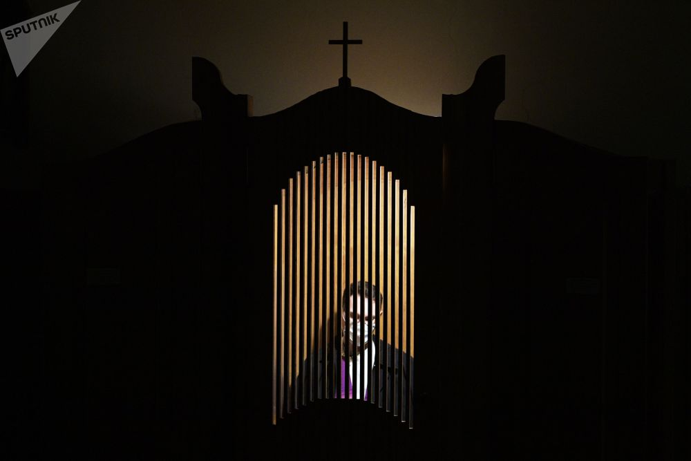 Священнослужитель в кабине для исповеди во время торжественной Рождественской мессы в Соборе Успения Пресвятой Девы Марии в Санкт-Петербурге (Россия)