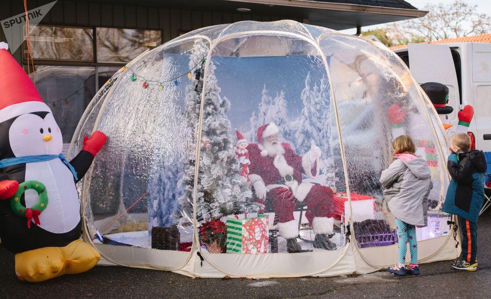 Мужчина в костюме Санта Клауса общается с детьми на украшенной к Рождеству улице в Сиэтле.