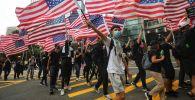 Протестующие размахивают национальными флагами США, маршируя к консульству США в Гонконге, чтобы призвать США оказать давление на Пекин, чтобы он выполнил их требования. 8 сентября 2019 года