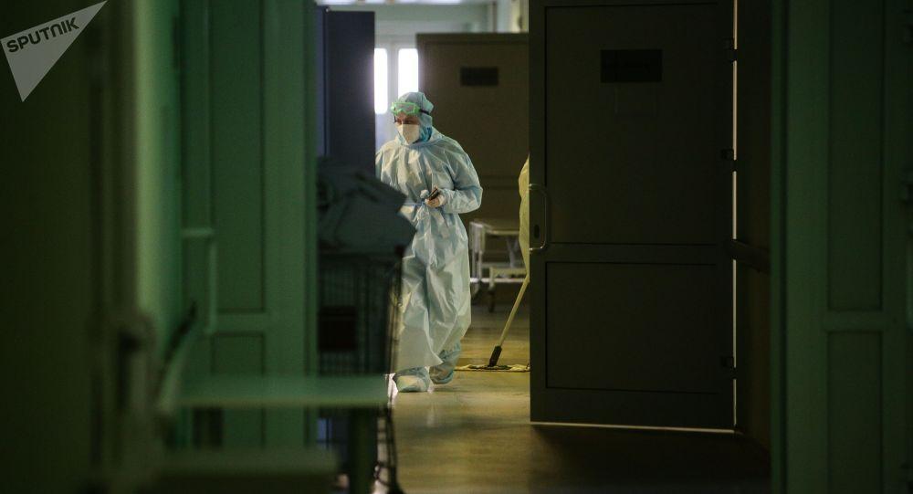 Медики в защитном противоэпидемическом костюме в коридоре клинической больницы.