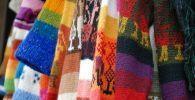 Разноцветные свитеры в вещевом магазине. Иллюстративное фото
