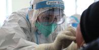 Медициналык кызматкер COVID-19 текшерүү үчүн адамдан анализ алып жатат