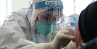 Медицинский работник берет мазок у человека для проверки на COVID-19