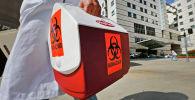 Медицинский сотрудник несет портативный холодильник с этикеткой биологической опасности. Архивное фото