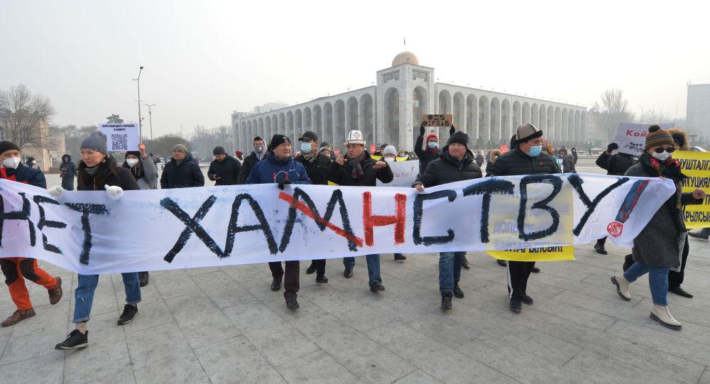 Люди держат плакат на митинге против новых конституционных поправок в Бишкеке