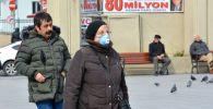 Женщина в защитной маске на одной из улиц в Стамбуле. Архивное фото