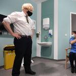 Улуу Британиянын премьер-министри Борис Жонсон вакцина алган адамды карап турат