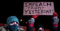 Женщина в защитной маске держит плакат во время митинга через день после штурма Капитолия сторонниками президента США Дональда Трампа
