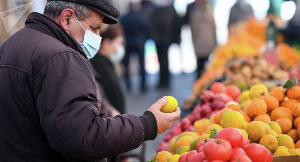 Покупатель выбирает лимон на продовольственной ярмарке. Архивное фото