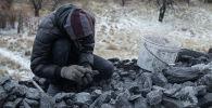 Мужчина собирает уголь. Архивное фото
