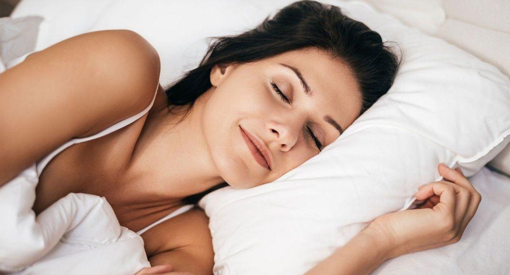 Девушка спит на кровати. Иллюстративное фото