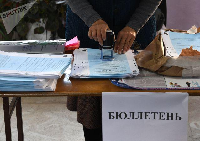 Женщина проштамповывает бюллетени во время подготовки избирательного участка в Бишкеке. Архивное фото