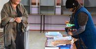 Бишкектеги шайлоо участкасында аялдар бюллетендерди даярдап жатышат. Архив