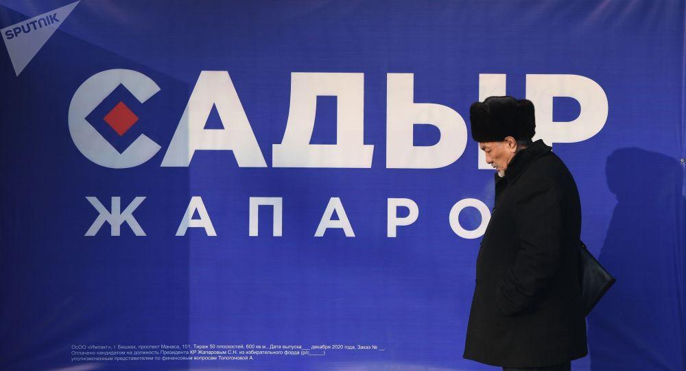 Шайлоодогу үгүт Садыр Жапаровдун билбордунун алдынан өтүп аткан киши. Архивдик сүрөт