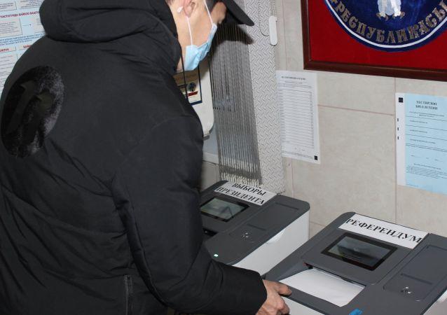 Гражданин КР во время голосования на выборах президента и референдума на избирательном участке в Москве