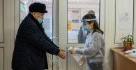 Мужчина дезинфицирует руки во время голосования на выборах президента и референдума на избирательном участке в Бишкеке