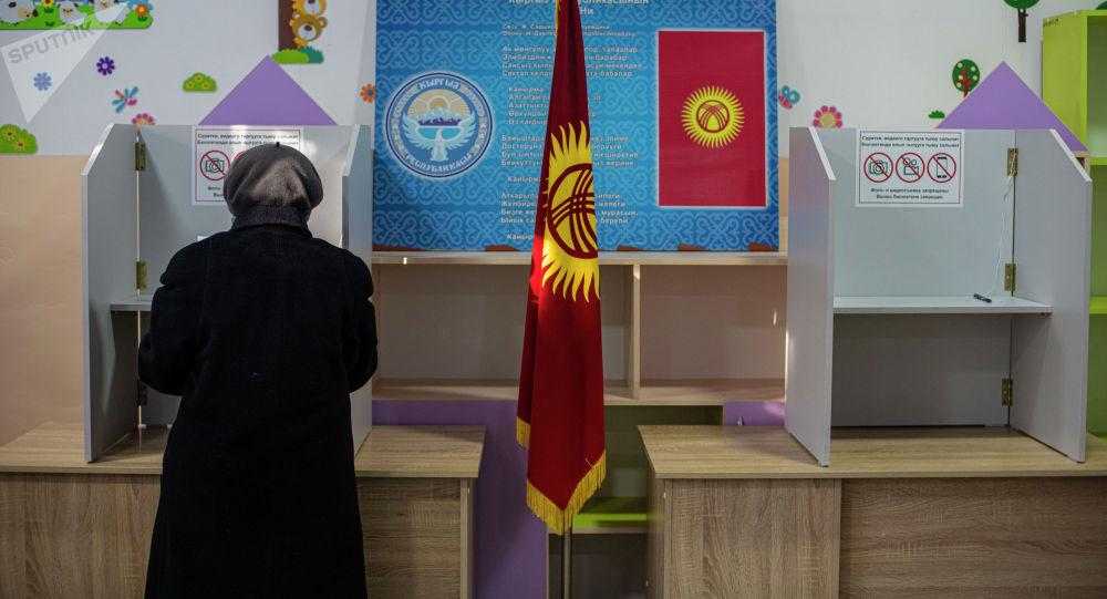 Женщина голосует на избирательном участке в Бишкеке во время выборов президента и референдума в Кыргызстане