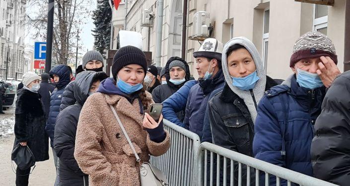 Люди стоят в очереди на избирательном участке в Москве во время выборов президента и референдума в Кыргызстане