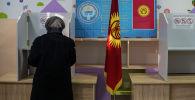 Бишкектеги шайлоо участогунда добуш берип жаткан аял