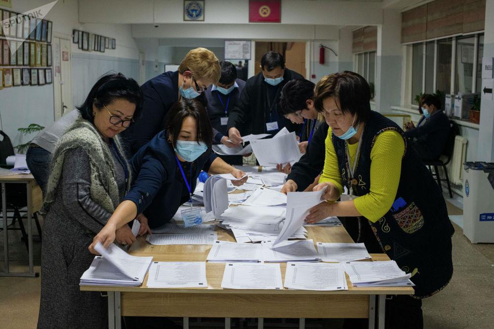 Сотрудники ЦИК во время подсчета голосов на избирательном участке в Бишкеке в ходе выборов президента и референдума в Кыргызстане