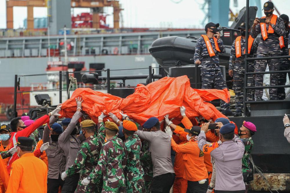 Спасатели несут найденные обломки в порту Джакарты во время поисковой операции рейса Sriwijaya Air SJY182, который разбился после взлета из Джакарты. 10 января 2021 года