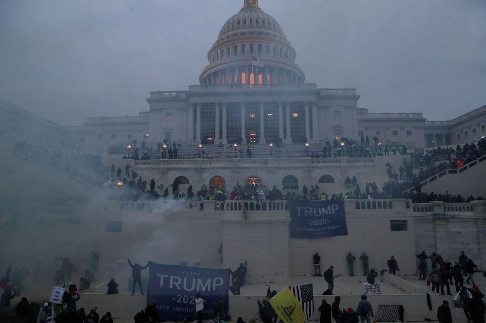 Полицейские стоят на страже, пока сторонники президента Дональда Трампа собираются перед зданием Капитолия в Вашингтоне (США) 06 января 2021 года