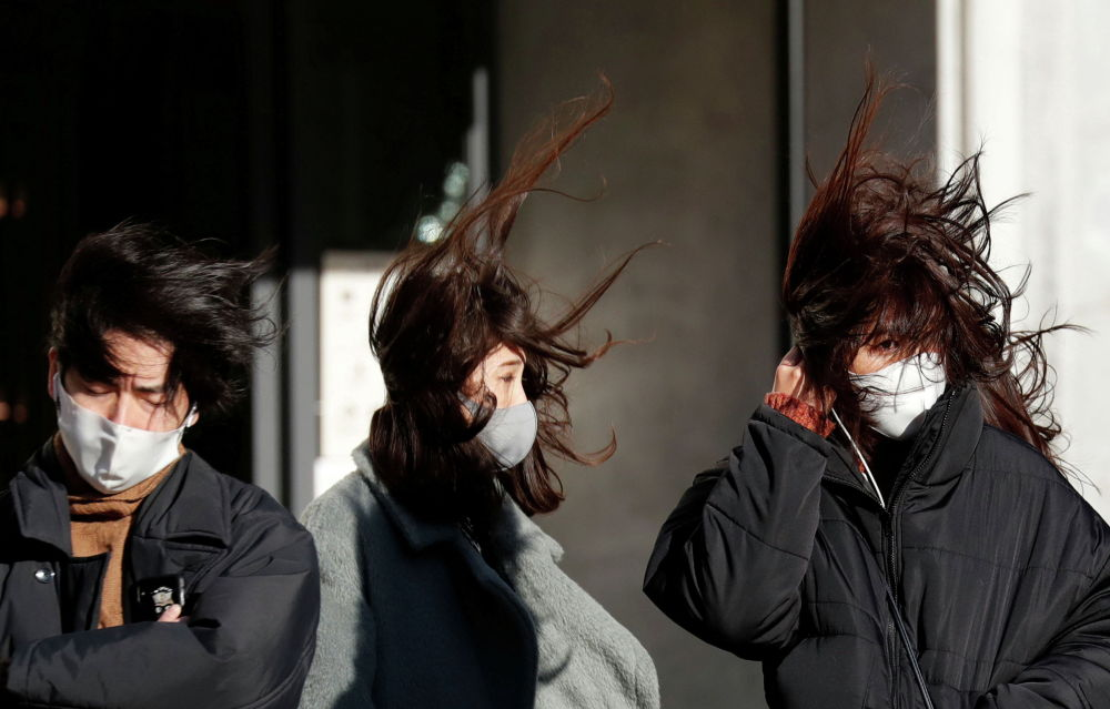 Пешеходы в защитных масках от COVID-19 стоят на сильном ветру в Токио (Япония) 07 января 2021 года