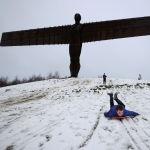Ребенок катается на санках после снегопада у скульптуры Ангела Севера в Гейтсхеде (Великобритания) 08 января 2021 года