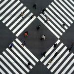 Люди, носящие защитные маски, чтобы помочь сдержать распространение коронавируса, ходят по пешеходным переходам в торговом квартале Гинза в Токио (Япония) 08 января 2021 года
