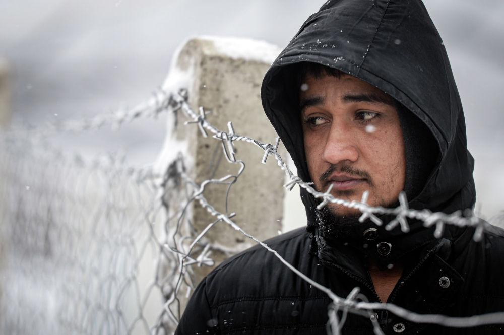 Мигрант стоит рядом с оградой во время снегопада в лагере Липа, недалеко от города Бихач (Босния и Герцеговина) 08 января 2021 года