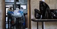 Сотрудники погребального агентства готовят тело умершего от COVID-19. Архивное фото