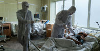 Медицинские работники в СИЗах лечат пациентов с COVID-19. Архивное фото