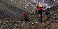 Путешественники едут на велосипедах по Алайским горам, Кыргызстан. Архивное фото