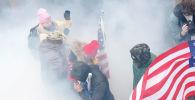 Протестующие, выступающие за Трампа в облаке слезоточивого газа во время столкновений с полицией у здания Капитолия в Вашингтоне