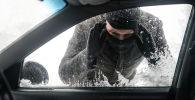 Мужчина имитирует вскрытие автомобиля. Архивное фото