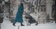 Женщина с коляской идет во время снегопада. Архивное фото