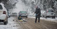 Женщина катает ребенка на санке во время январского снегопада в Бишкеке