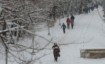 Люди идут по тротуару в Бишкеке