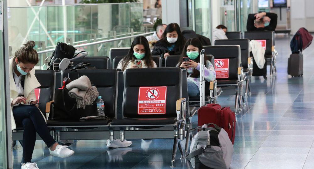 Пассажиры в медицинских масках в холле международного аэропорта Ханэда в Токио, Япония