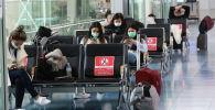 Япониянын Токио шаарындагы Ханэда эл аралык аэропортунда беткап кийген жүргүнчүлөр
