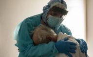 Медициналык кызматкер COVID-19 менен ооруган бейтапты кучактап жатат. Архив