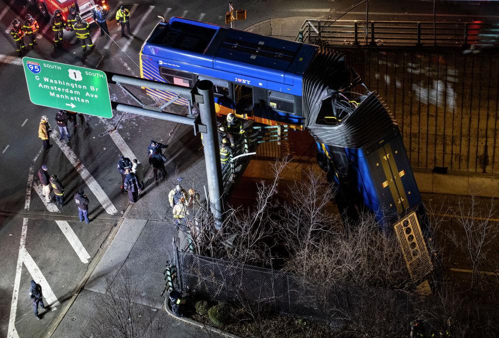 Нью-Йоркто жүргүнчү ташыган автобус кырсыктап, көпүрөгө асылып калды