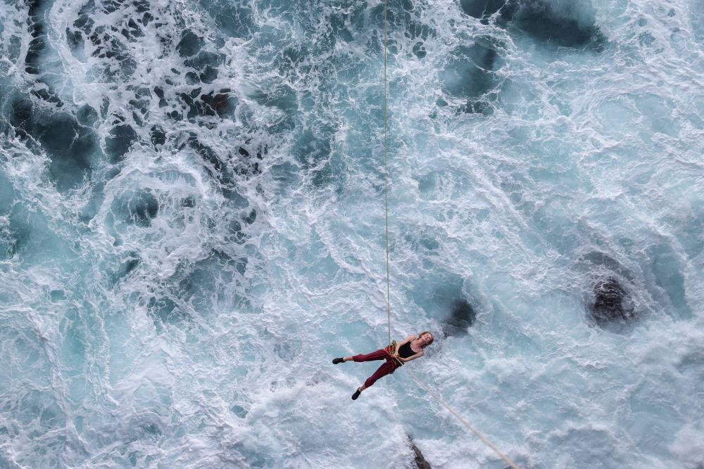 Суунун үстүнө тартылган аркан менен секирген спортчу. Австралия