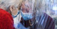 Жительница дома престарелых Доменико Сартор обнимает свою приехавшую дочь через пластиковую ширму. Архивное фото