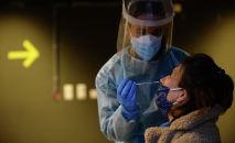 Медицинский работник берет у женщины образец мазка из носа для теста на COVID-19. Архивное фото