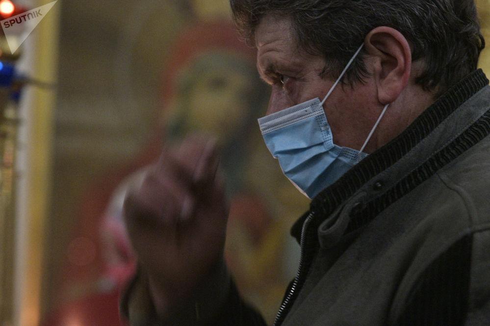 Мужчина молится во время празднования Крещение Господне в Свято-Воскресенском кафедральном соборе в Бишкеке