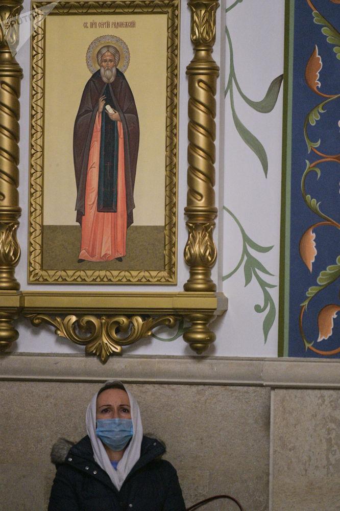 Женщина на фоне иконы святого во время празднования Крещение Господне в Свято-Воскресенском кафедральном соборе в Бишкеке