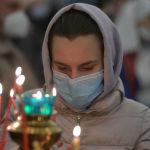 Женщина ставит свечу во время празднования Крещение Господне в Свято-Воскресенском кафедральном соборе в Бишкеке